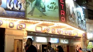 People walk past a poster of the movie outside a cinema in Cairo