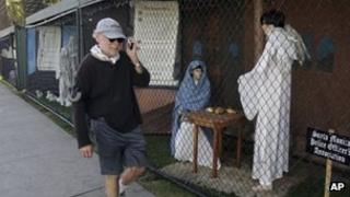 A man walks past two of the traditional Nativity scenes along Ocean Avenue at Palisades Park in Santa Monica, California 13 December 2011