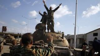Syrian fighters celebrate after storming a military base in Aleppo on 19/11/12
