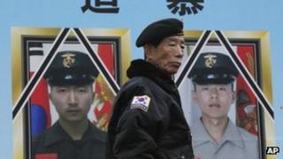 A South Korean veteran stands in front of portraits of two marines killed on Yeonpyeong island, at a rally in Seoul on 22 November 2012