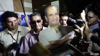 Farc delegate Ruben Zamora (centre, in sunglasses) carries a life-size cardboard cut-out of imprisoned guerrilla Simon Trinidad before talks in Havana, Cuba, 19 November 2012