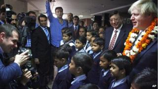 London Mayor Boris Johnson, right, poses for photographers with Indian schoolchildren at the Amity University on the outskirts of New Delhi