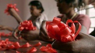 HIV positive women make red ribbons, the universal symbol of awareness and support for those living with HIV