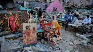 Pakistani Hindus sit next to a demolished Hindu temple in Karachi on December 2, 2012
