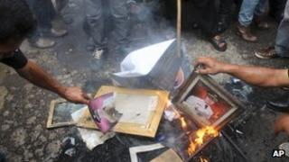 Protesters burn portraits of Garut District Chief Aceng Fikri during a protest in the town of Garut, West Java, Indonesia, Tuesday, Dec. 4, 2012.