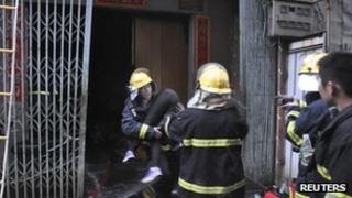 Fire fighters carry a victim of the Shantou city blaze