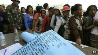 A list of missing people is prepared as residents line up for relief supplies in New Bataan on Thursday 6 December