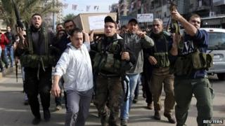 Lebanese Islamist gunmen carry the coffin of a man recently killed in Syria through the city of Tripoli (10 December 2012)