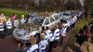 Children dressed in SC Buitenboys colours pay respect to Dutch linesman Richard Nieuwenhuizen as the hearse carrying his body arrives at the crematory in Almere, 10 December 2012