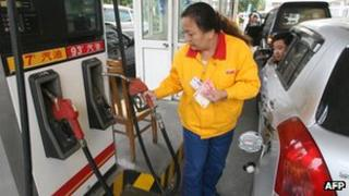 An attendant filling petrol at a fuel station in China