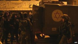 Israeli soldiers gather next to their vehicle during clashes with Palestinians in the West Bank town of Hebron, 12 December 2012