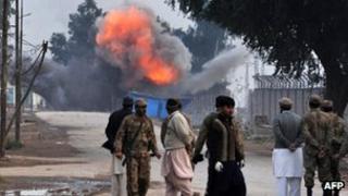 Onlookers observe a controlled blast at Peshawar airport perimeter