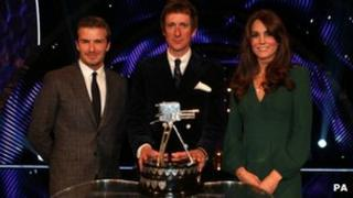 Bradley Wiggins holding the Sports Personality of the Year Trophy on stage with the Duchess of Cambridge and David Beckham