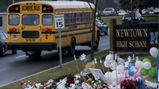 School bus drives past Newtown High School sign