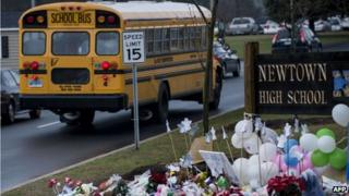 A school bus passes a makeshift memorial to the victims of the Sandy Hook Elementary School shooting as it takes students to Newtown High School 18 December 2012