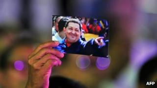 A woman holds a picture of Hugo Chavez at a concert in his honour