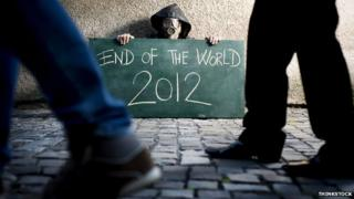 """Man in gasmask holding """"End of the world 2012"""" sign"""