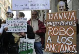 "People hold placards reading ""Bankia steal elderly people"" and ""Rato thief"" during a demonstration against Bankia and former IMF chief Rodrigo Rato in front of Spain""s National Court in Madrid"