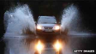 A vehicle drives through flood waters from the River Thames in Sonning, England