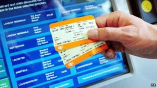 Rail tickets held out in front of ticket machine