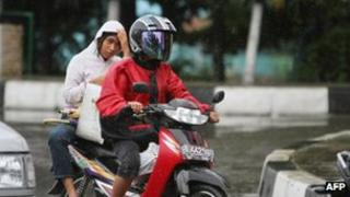 An Acehnese woman rides on the back side of a motorcycle in Banda Aceh, 2 January 2013.