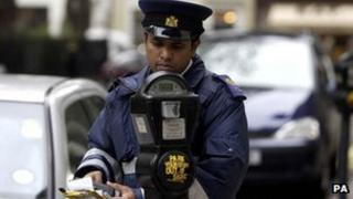 Traffic warden checking parking meters in central London