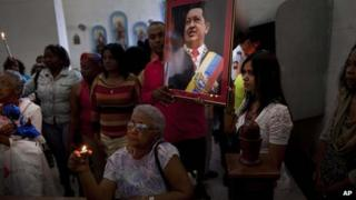 Venezuelan embassy workers in Cuba hold up picture of Chavez during a service for the sick, 8 January