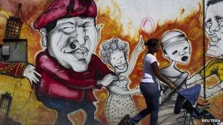 Woman walks past a mural of Hugo Chavez