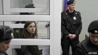 "Maria Alyokhina, a member of the female punk band Pussy Riot, looks out from a defendants"" box during a court hearing in Berezniki in Perm region, near the Ural mountains, 16 January 2013"