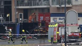Firefighters walk past a section of a damaged crane