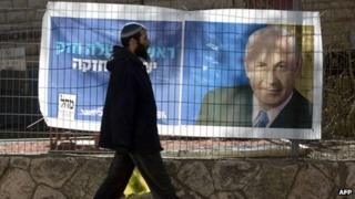 Man walks past election poster of Benjamin Netanyahu, in Kiryat Arba settlement (15/01/13)