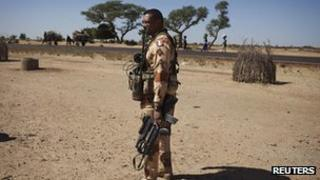 A French soldier holds his weapon in the village of Sarakala, Mali