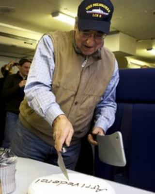 Leon Panetta cuts a cake that says 'arrivederci' on his final overseas trip as US Defence Secretary, aboard the E-4B on route to Washington, 19 January 2012