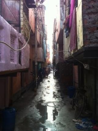 The narrow wet and muddy lane where the victims' family live in Delhi