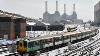 Trains on snowy tracks near London Victoria Station and Battersea Power Station