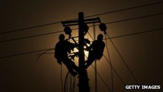Workers fix power supply wires on a pole in China