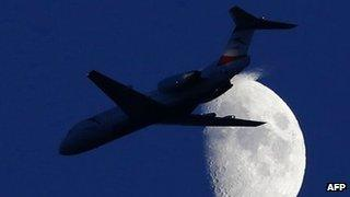 A commercial plane flying in front of the moon