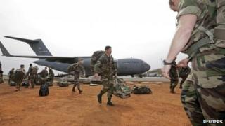 French soldiers carry their equipment after arriving on a US C17 transport plane at the airport in Bamako 22 January 2013