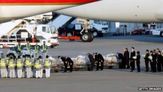 Officers bow their heads as they place flower bouquets on coffins of Algerian hostage crisis victims