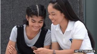 Women in Thailand use a mobile phone
