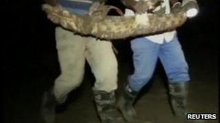 Screengrab from Reuters showing workers at the Rakwena Crocodile Farm with a captured crocodile