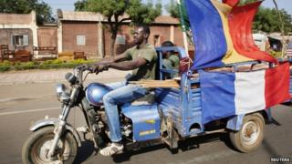 A man drives a motorbike in Mali's capital, Bamako, decorated with French flags among others to show his support for the international forces -24 January 2013