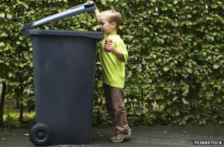 Boy putting a can in a bin
