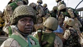 Nigerian soldiers unload their equipment as they arrive at the Mali air force base near Bamako 19 January 2013