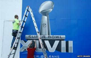 Workers finish a Super Bowl sign prior to the start of Super Bowl XLVII in New Orleans
