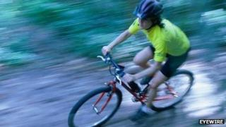 Person riding a bike through a forest