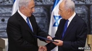 Israeli Prime Minister Benjamin Netanyahu (L) receives a folder from President Simon Peres at the president's residence in Jerusalem on 2 February 2013