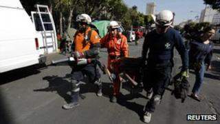 Rescue workers carrying equipment at the site of Thursday's blast in Mexico City
