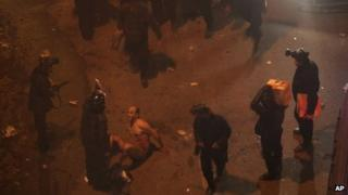 Egyptian riot police beat naked Hamada Saberon 1 February 2013 in Cairo