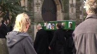 Coffin being carried into church while people stand in the background